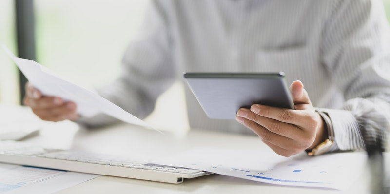 holding a tablet and paper