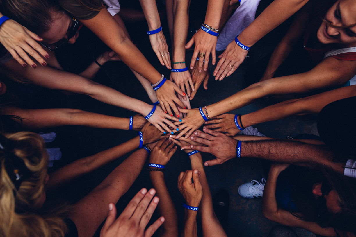 people with hand together in huddle